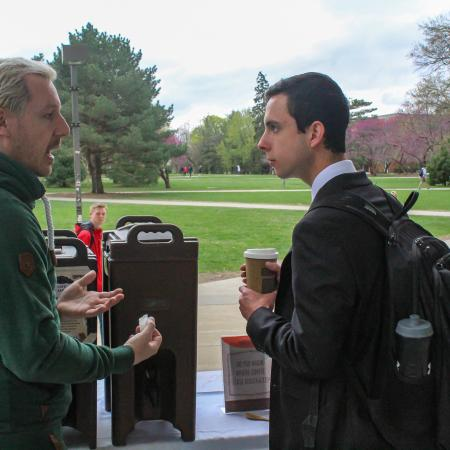 Two students have conversation over coffee.