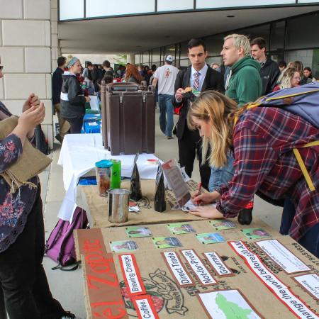 Tables supplied with student organization fliers are viewed by participants.