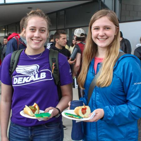 Two students with plates of food enjoy the celebration event.