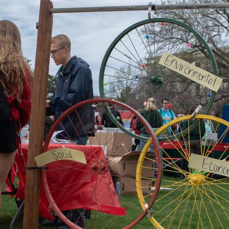 The event hosted a sculpture of bike rims that created the Sustainability Venn Diagram and how each table represented fits into that diagram.